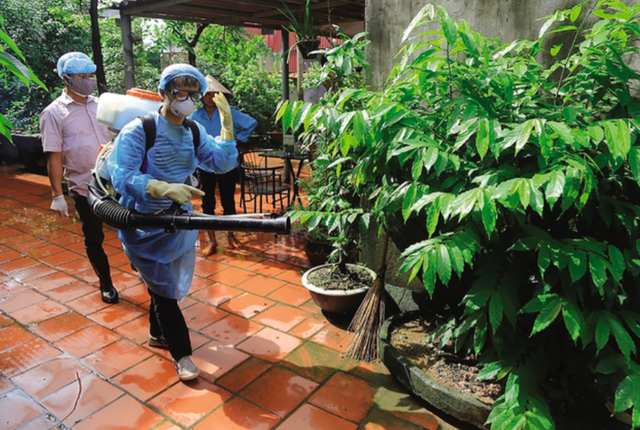 Cán bộ y tế dự phòng Hà Nội phun thuốc diệt muỗi tại nhà dân.     Ảnh: TL