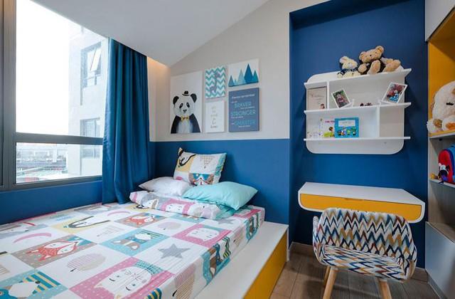 Căn phòng của cậu con trai 5 tuổi có phần vui nhộn hơn với nhiều mảng màu hơn, dù vẫn là xanh - vàng. Gầm giường được thiết kế thêm ngăn chứa đồ để tăng diện tích sử dụng tối đa.