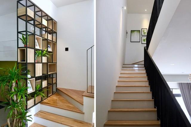 Ngôi nhà càng trở nên xanh mát hơn với kệ gỗ trồng cây và bộ tranh lá tại lối dẫn lên tầng 2. Lan can cầu thang với các thanh đứng để hạn chế trẻ nhỏ leo trèo nguy hiểm.