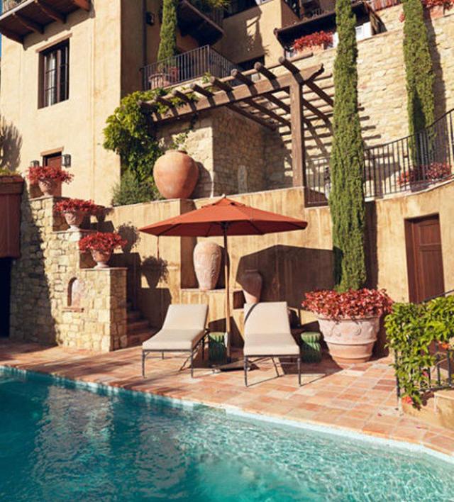 Thiết kế hồ bơi kiểu Tuscan với những ô màu cam và cây bách, sau đó mang thêm một ly rượu vang đỏ đến hồ bơi, bạn sẽ có thời gian nghỉ ngơi hoàn hảo.