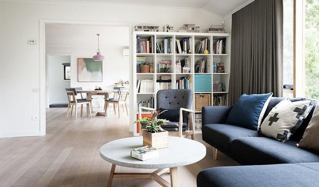 Bên trong ngôi nhà được thiết kế đơn giản với nội thất hiện đại. Sofa và bàn trà khung gỗ sồi chắc chắn giúp mặt bàn đá và ghế sofa bằng nệm nỉ màu xanh thêm nổi bật.