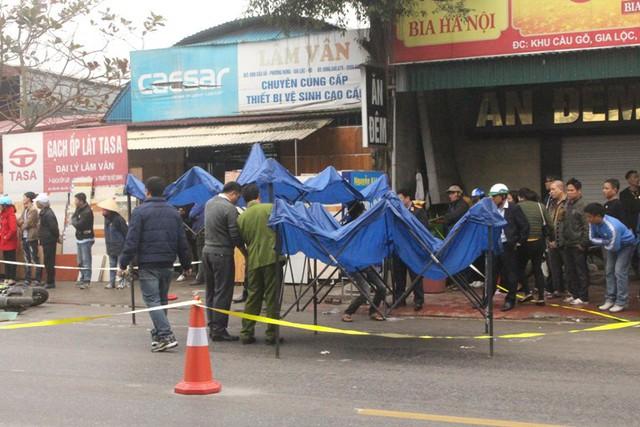 Lực lượng chức năng tiến hành khám nghiệm hiện trường và căng bạt che mưa khám nghiệm tử thi