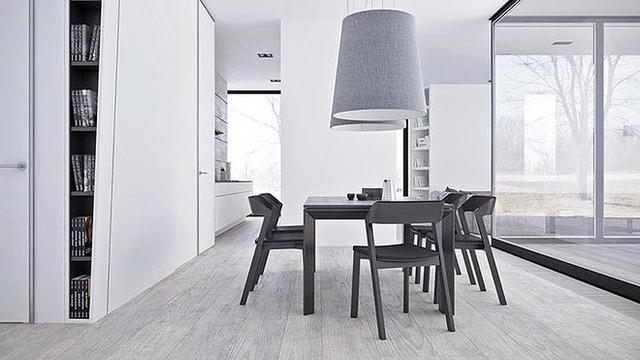 Một bộ ghế phong cách Scandinavia và bàn ăn là những đồ có màu tối nhất trong phòng. Hai chiếc đèn mặt dây chuyền màu xám khổng lồ tạo thêm sự bất cân xứng khác lạ cho căn phòng.