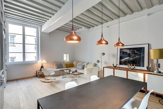 Ánh sáng mặt dây chuyền bằng đồng đẹp cho khu vực ăn uống bên trong căn hộ nhỏ ở Paris.