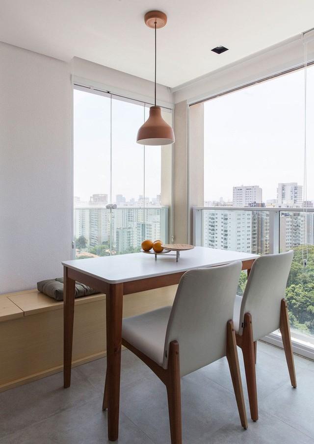 Ăn uống nhỏ được đánh bóng trong góc căn hộ với tích hợp lưu trữ và cảnh quan thành phố.