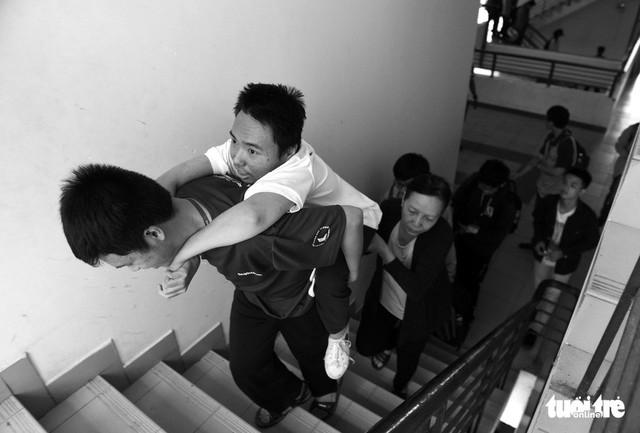 Người mẹ miệt mài cõng con bại liệt đến giảng đường đại học - Ảnh 1.