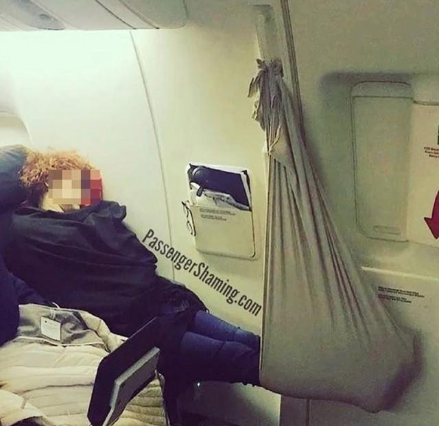 Hành khách dùng chăn làm võng ngủ trên máy bay gây tranh cãi - Ảnh 1.