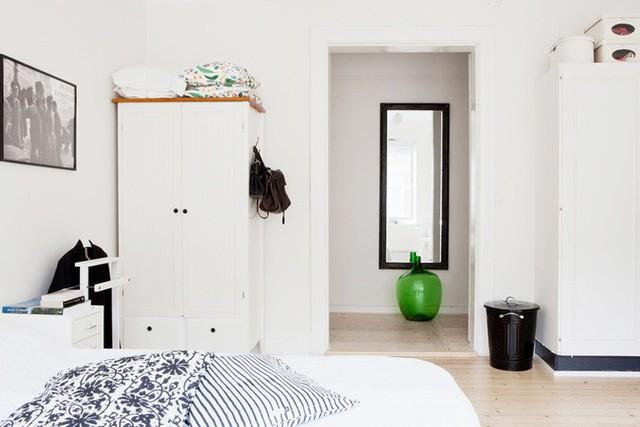 Tận dụng hai bên tường sát cửa, chủ nhân của căn hộ đã khéo léo bố trí tủ đựng đồ. Tủ được chọn cùng tone màu với tường giúp cho căn phòng rộng rãi, thông thoáng hơn.