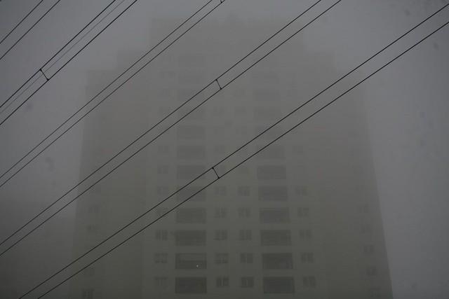 Cận cảnh một tòa nhà cao 30 tầng bị sương mù bao phủ.
