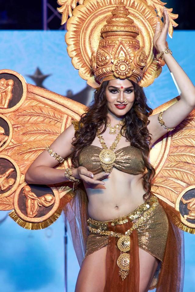 Thí sinh Ấn Độ - Veena Sendre chọn phong cách gợi cảm, trang phục thiết kế độc đáo, đặc biệt là phần mũ. Tuy nhiên, cô lộ nhược điểm vòng eo quá to khi mặc đồ diễn táo bạo.