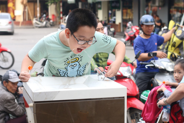 Nguồn nước mát lạnh, thanh khiết khiến trẻ em vô cùng thích thú. Trụ nước được lắp đặt gần trường học, giúp các em dễ dàng sử dụng nước trong mỗi giờ tan trường. Ảnh: Thu Phương