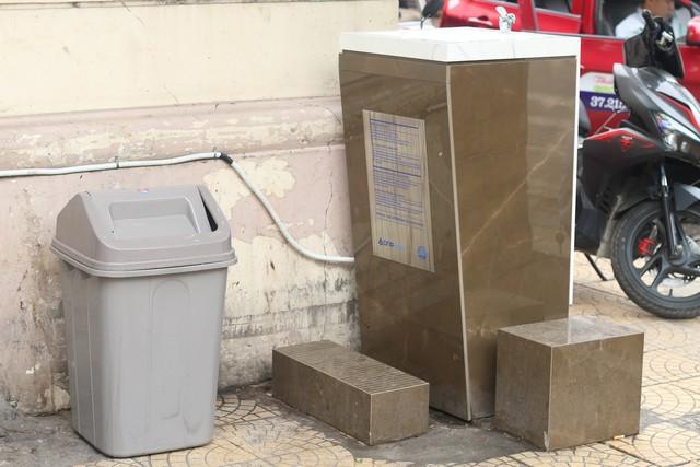 Ngoài ra, tại chợ Đồng Xuân, trụ nước sạch được đặt ngay cạnh thùng rác cũng gây mất vệ sinh cho nguồn nước bởi mùi hôi và ruồi nhặng bốc lên từ rác thải. Ảnh: Thu Phương