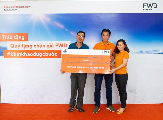 Bà Vương Mỹ Phụng - Phó Tổng Giám đốc Bộ phận Chiến lược Tiếp thị và Thương hiệu FWD Việt Nam và Phan Thanh Nhiên đã trao số tiền của Quỹ tặng chân giả cho đại diện Trung tâm Nghiên cứu và Phát triển năng lực người khuyết tật là ông Nguyễn Văn Cử - Phó Giám Đốc Trung tâm.
