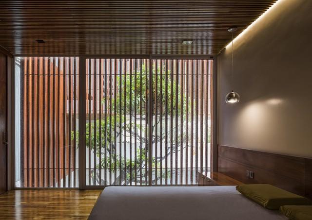 Lên những tầng trên, bên ngoài lớp cửa kính còn có một hệ lam gỗ để giảm bớt ánh sáng và nắng nóng trong mùa hè.