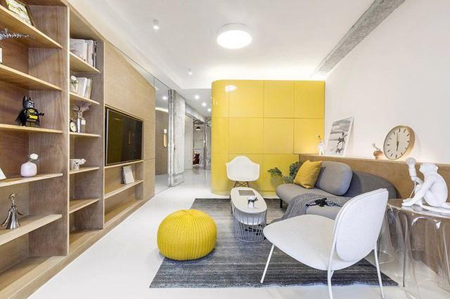 Màu vàng của hộp nhà bếp được bổ sung bởi các điểm nhấn màu gỗ sáng, màu xám và bề mặt trắng sắc nét.