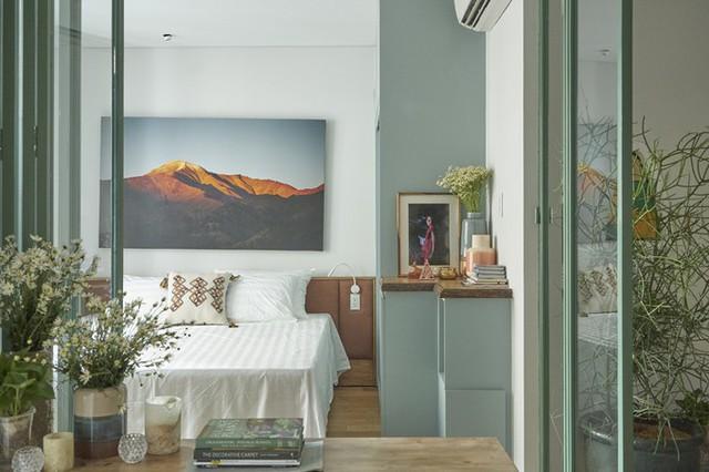 Bức tường ngăn cách phòng ngủ và không gian chung được đập bỏ, thay vào đó là hệ cửa lùa bằng gỗ và kính, khiến tất cả các không gian chức năng như liền vào một, làm tăng chiều sâu cho không gian chung.