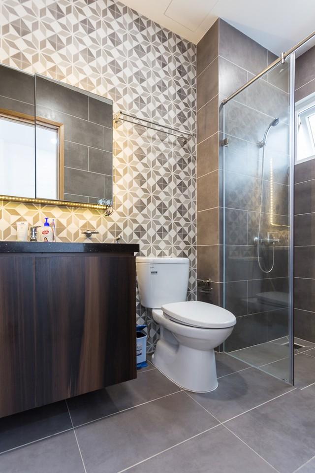 Nhà vệ sinh bên cạnh nội thất bằng gỗ, ở khu vực thường xuyên tiếp xúc với nước còn có gạch ốp tường và lát sàn màu nâu giả gỗ cũng tạo nên sự đồng nhất trong trang trí ở lầu 1.