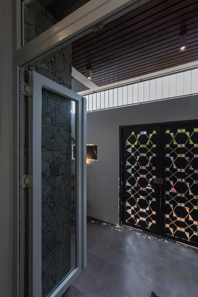 Cánh cửa sắt với những lỗ thông hơi nhiều kiểu hình khối chính là một lam gió nơi tầng trệt. Khi ánh nắng xuyên qua những lỗ thông hơi, cánh cửa đa sắc như một chiếc kính vạn hoa.
