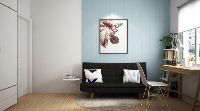 Phòng làm việc nhẹ nhàng, yên tĩnh với bàn gỗ đặt gần cửa sổ, ghế sofa màu xám đen đặt dưới bức tường màu xanh.