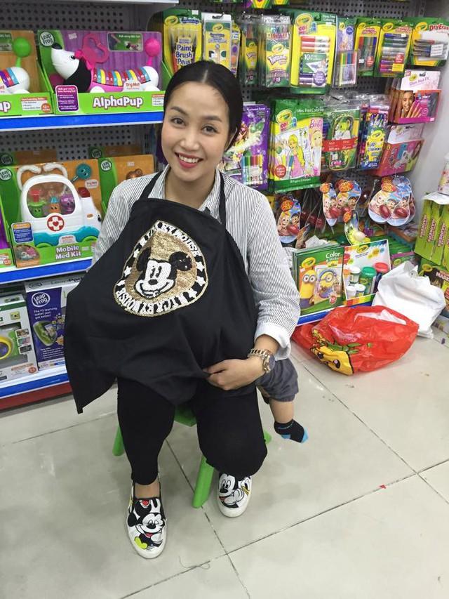 Ốc Thanh Vân tranh thủ cho con bú khi đi mua sắm.