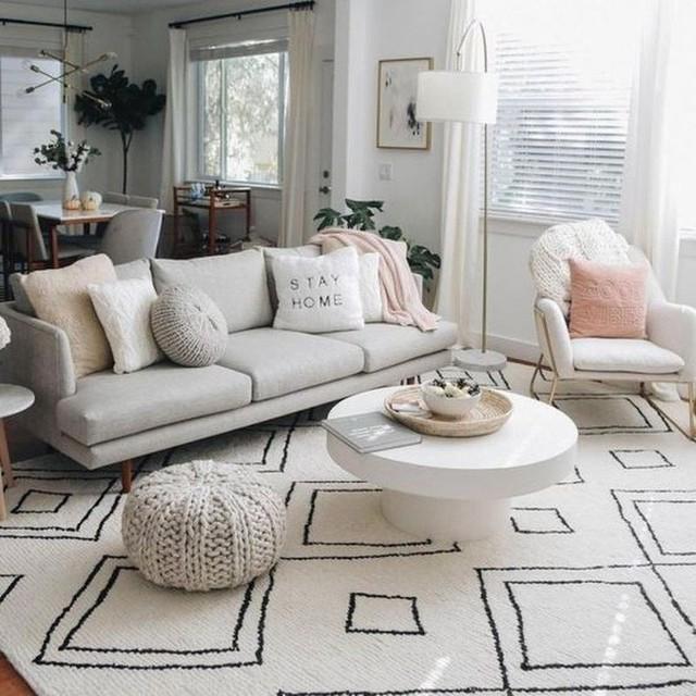 Phòng khách sáng sủa với ghế sofa và gối màu trắng không chỉ là một trung tâm mà còn là một vách ngăn giữa phòng khách và nhà bếp.