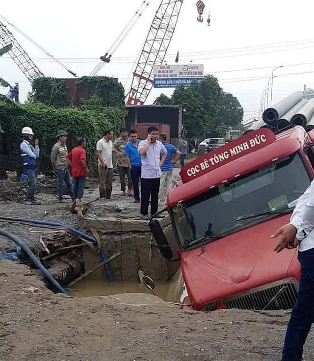 Chiếc xe container sụt lún xuống hố sâu ở gần chân cầu vượt Phú Thụy.
