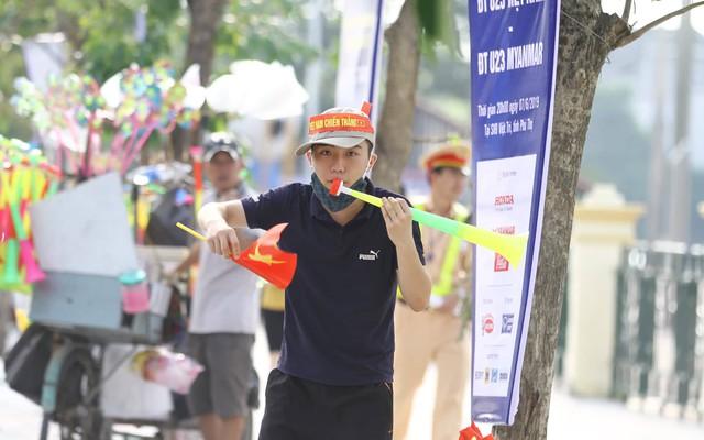 Một nam thanh niên cố gắng thổi kèn nhựa khuất động không khí.