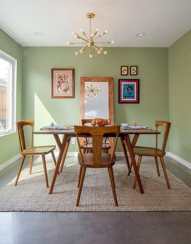 Phòng ăn hiện đại với một chiếc gương lớn đặt ngay chính giữa của ngôi nhà. Thiết kế nội thất mạnh mẽ được cân bằng ngay lập tức nhờ màu xanh nhạt dịu dàng.