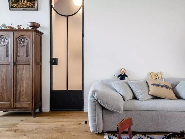 Khác với nhiều căn hộ khác, căn hộ được bố trí phòng khách ở khu vực trung tâm, nơi mọi người có thể đi từ bất kỳ khu vực chức năng nào cũng có thể dừng lại ở phòng khách, ngồi ở sofa văng nỉ xinh xắn và ngắm nhìn không gian sống thân thuộc của mình. Góc tiếp khách không quá cầu kỳ mà chỉ gói gọn những nội thất cơ bản nhất để tầm nhìn cho toàn bộ không gian được thoáng sáng và đẹp mắt.