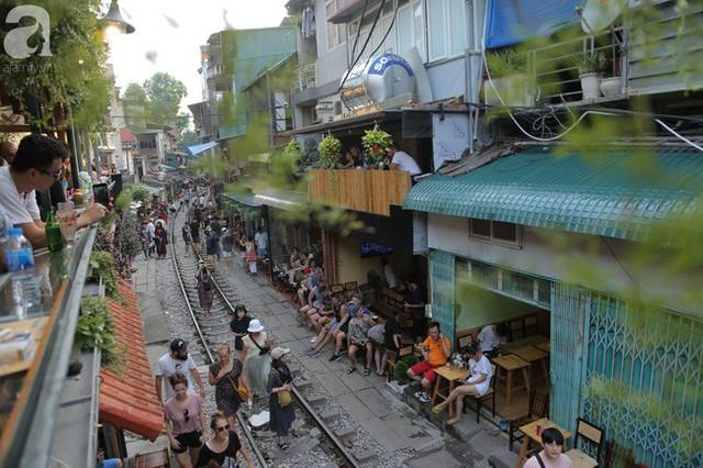 Hà Nội: Bất chấp nguy hiểm, khách du lịch vẫn thản nhiên chụp ảnh, ăn uống ngay sát đường ray tàu - Ảnh 2.