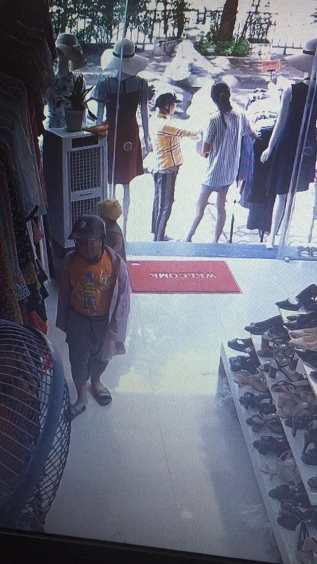 Xôn xao đoạn clip mẹ giả vờ xem đồ, xúi con nhỏ trộm điện thoại trong shop quần áo - Ảnh 1.