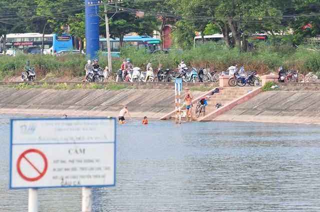 Trời oi bức, người dân tấp nập ra hồ Linh Đàm lặn ngụp dù biển cấm cắm khắp nơi - Ảnh 3.