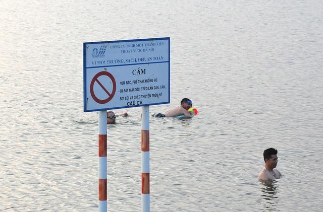 Trời oi bức, người dân tấp nập ra hồ Linh Đàm lặn ngụp dù biển cấm cắm khắp nơi - Ảnh 7.