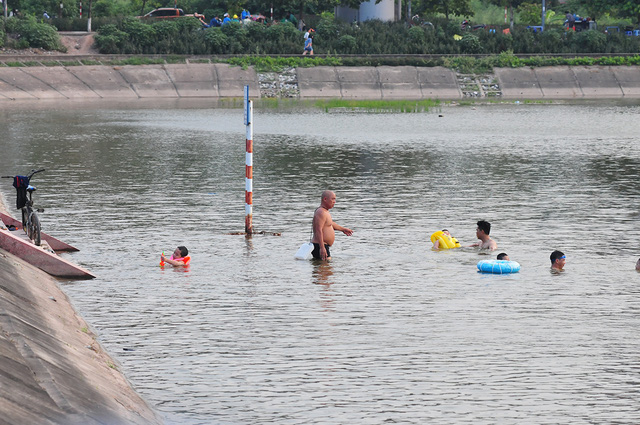 Trời oi bức, người dân tấp nập ra hồ Linh Đàm lặn ngụp dù biển cấm cắm khắp nơi - Ảnh 2.