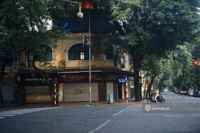 Hà Nội ngày đầu thực hiện giãn cách xã hội theo Chỉ thị 16: Đường phố vắng lặng, hàng quán đóng kín cửa im lìm - Ảnh 4.