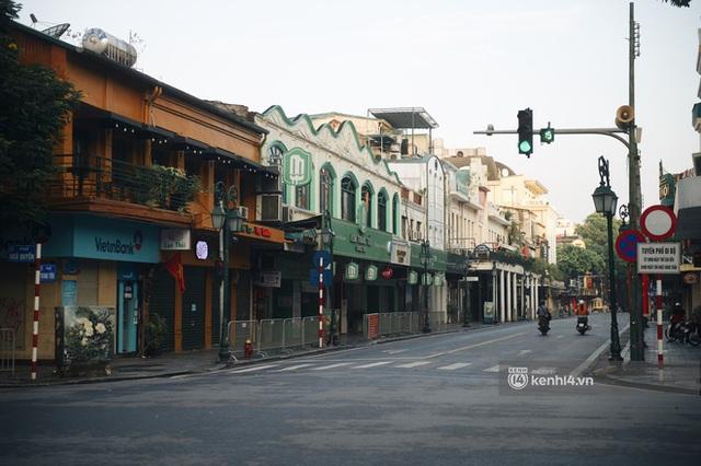 Hà Nội ngày đầu thực hiện giãn cách xã hội theo Chỉ thị 16: Đường phố vắng lặng, hàng quán đóng kín cửa im lìm - Ảnh 5.