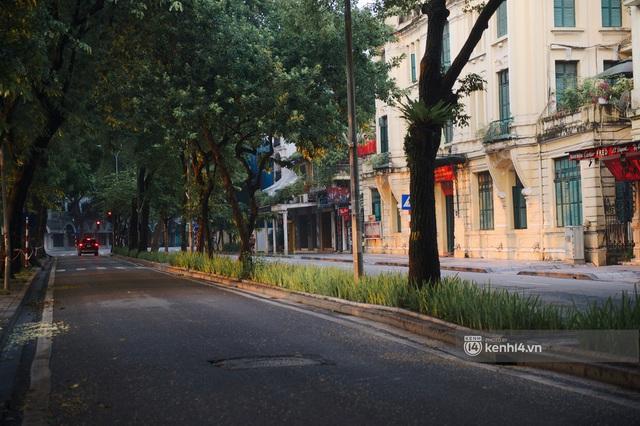 Hà Nội ngày đầu thực hiện giãn cách xã hội theo Chỉ thị 16: Đường phố vắng lặng, hàng quán đóng kín cửa im lìm - Ảnh 7.