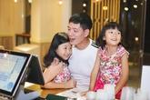 Bình Minh hai tay bế hai con gái đứng chọn trà sữa