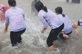 Mặc mưa ngập đến cả đầu gối, hàng chục học sinh vẫn vô tư chơi đùa dưới sân trường: Vui nhưng có an toàn?