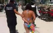 Cô gái trẻ mặc bikini ngồi dưới gốc cây bị bắt