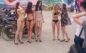 Dàn chân dài mặc đồ lót, dắt xe, giới thiệu hàng tại một siêu thị