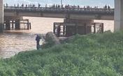 Hàng chục người tụ tập trên cầu xem vớt thi thể trôi sông