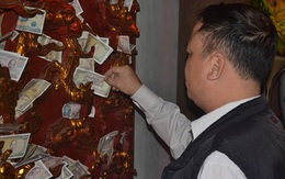 Du khách thi nhau nhét tiền vào mắt rồng để cầu may