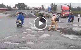CSGT đẩy xe rùa, cầm cuốc san lấp ổ gà trên quốc lộ