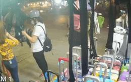 Cô gái đang lúi húi mải chọn túi xách, không hề biết chuyện tồi tệ đang diễn ra ngay sau lưng mình