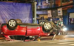 TP.HCM: Ô tô húc văng cột đèn rồi lật ngửa, 2 người bò ra khỏi xe kêu cứu