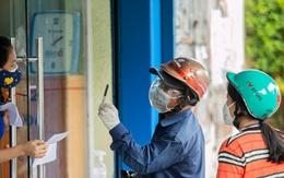 Ảnh: Cha mẹ loay hoay mua sách qua hàng rào cho con học online trong những ngày giãn cách ở TP.HCM