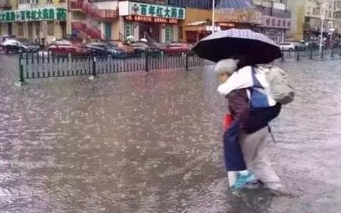 Bức ảnh bà lội nước cõng cháu gái lớn đi học khiến dư luận dậy sóng
