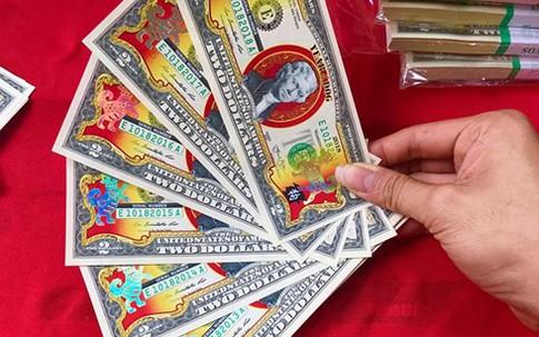 Chi tiền triệu mua 2 USD hình chó mạ vàng biếu Tết